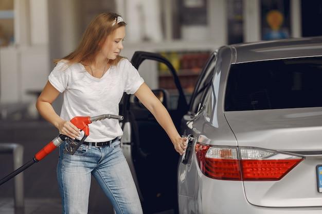 Mulher elegante, de pé em um posto de gasolina