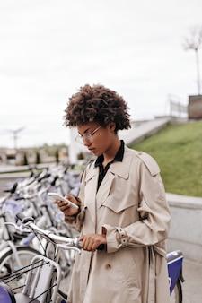 Mulher elegante de pele escura usando óculos segurando um telefone