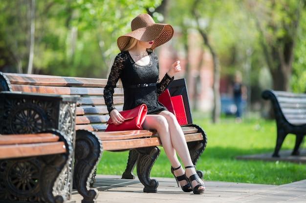 Mulher elegante de vestido preto e chapéu com sacolas de compras, sentada em um banco do parque
