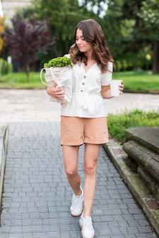 Mulher elegante de vista frontal carregando compras
