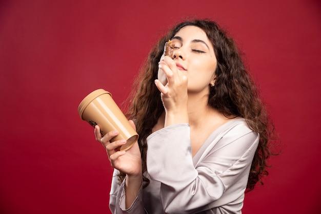 Mulher elegante, desfrutando de seu café e chocolate.