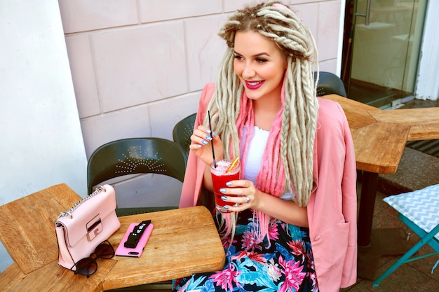 Mulher elegante desfrutando de sua saborosa limonada de baga no terraço do café
