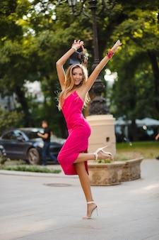 Mulher elegante e atraente e elegante em um vestido rosa sexy de verão andando na rua segurando uma bolsa com as mãos no ar