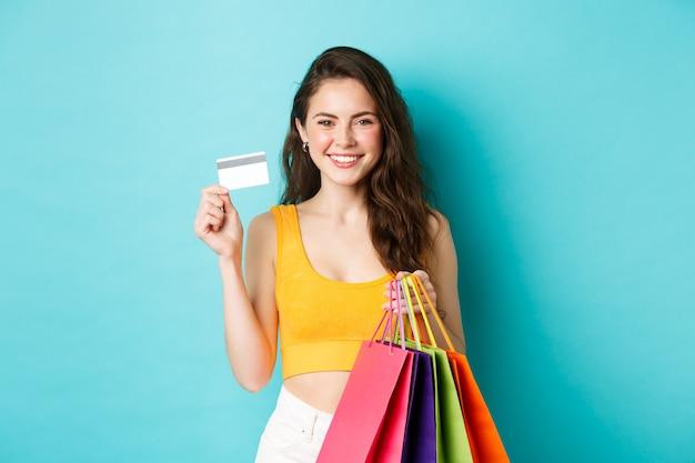 Mulher elegante e atraente mostrando um cartão de crédito de plástico que ela usou para pagar por roupas novas, segurando sacolas de compras com mercadorias, em pé sobre um fundo azul