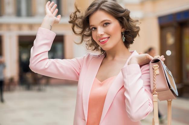Mulher elegante e atraente sorridente com penteado encaracolado caminhando pela cidade com uma bolsa estilosa rosa