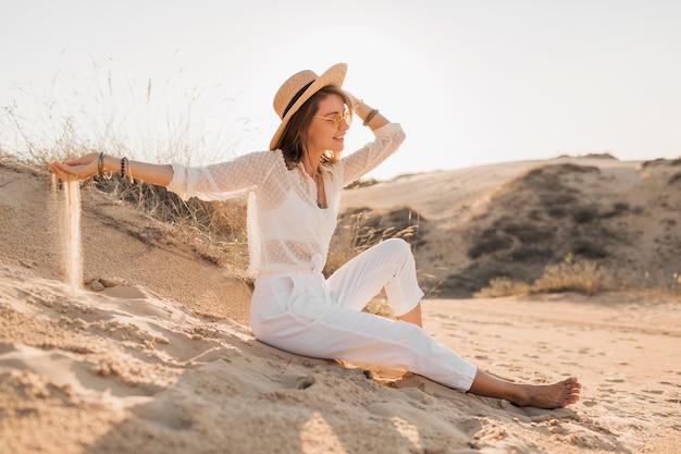 Mulher elegante e atraente sorridente posando na areia do deserto, vestida com roupa branca, chapéu de palha e óculos escuros no pôr do sol