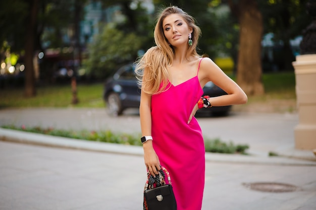 Mulher elegante e atraente usando um vestido rosa sexy de verão andando na rua segurando uma bolsa Foto gratuita