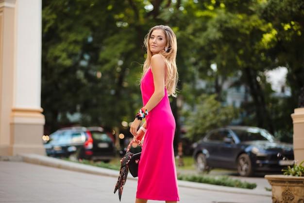 Mulher elegante e atraente usando um vestido rosa sexy de verão andando na rua segurando uma bolsa
