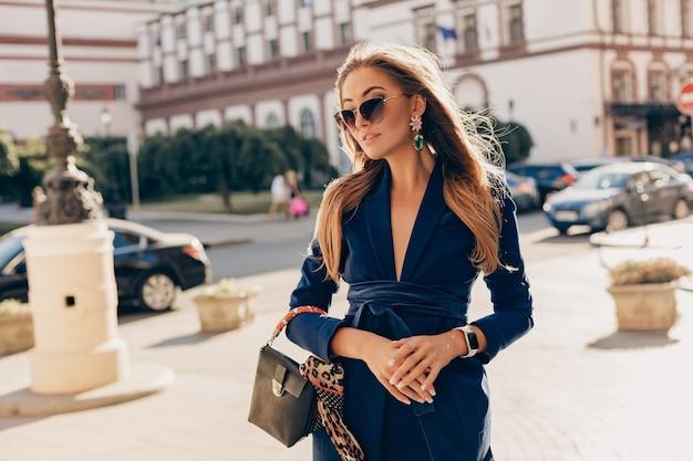 Mulher elegante e atraente vestindo um terno azul elegante e óculos escuros andando na rua segurando uma bolsa