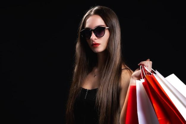 Mulher elegante e bonita com sacola de compras em fundo preto