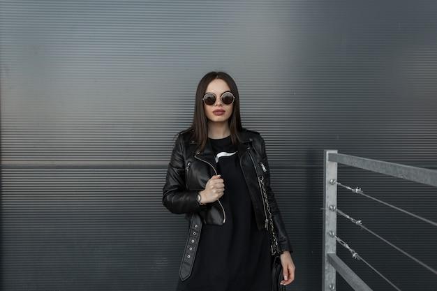 Mulher elegante e bonita hippie em óculos de sol redondos da moda e jaqueta de couro preta com moletom fica perto de uma parede de metal na cidade