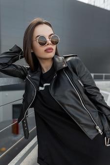 Mulher elegante e bonita modelo com rosto natural bonito com óculos vintage na elegante jaqueta de couro preta e moletom de tecido na cidade