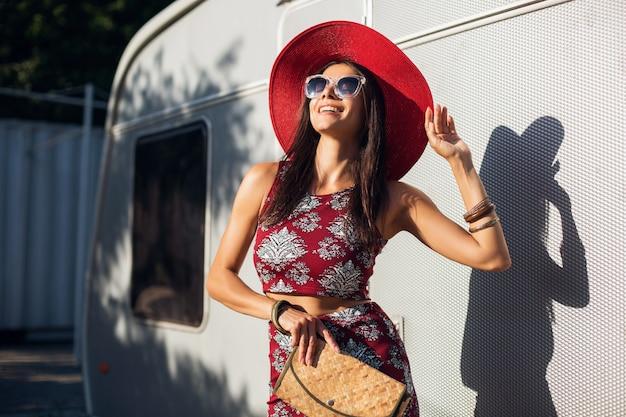 Mulher elegante e bonita posando contra um trailer prateado com roupa de estilo tropical