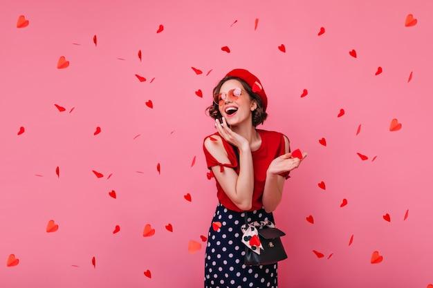 Mulher elegante e despreocupada posando no dia dos namorados. rindo glamourosa garota encaracolada na boina em pé sob confete vermelho.