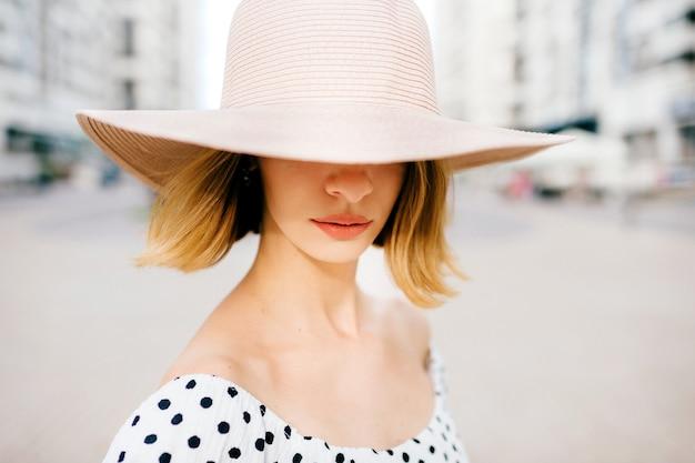 Mulher elegante e elegante de cabelo curto loira com chapéu e vestido posando sobre o fundo da rua