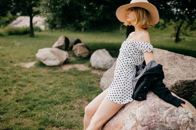 Mulher elegante e elegante de cabelo curto loira com chapéu posando nas pedras do parque