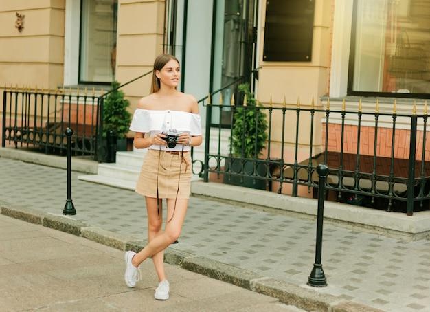 Mulher elegante e elegante em roupas da moda e óculos escuros posando ao ar livre