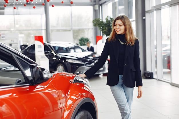 Mulher elegante e elegante em um salão de automóvel