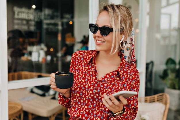 Mulher elegante e estilosa usando óculos escuros pretos e um vestido moderno brilhante com uma xícara de café