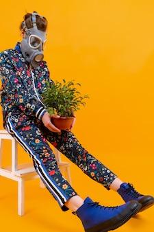 Mulher elegante e estranha no respirador sentada na escada com uma flor no vaso sobre uma parede laranja