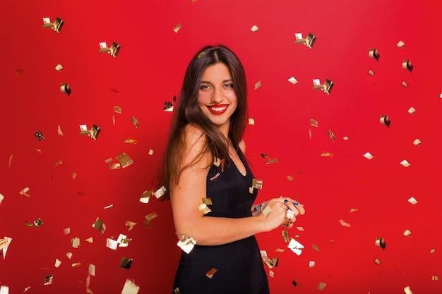 Mulher elegante e feliz com batom vermelho, vestido preto posando em vermelho com confete e faíscas