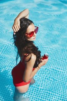 Mulher elegante e feliz modelo morena com uma figura sexy perfeita em elegante maiô vermelho e óculos de sol vermelhos na moda na piscina com uma bebida gelada na mão
