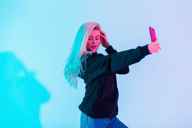 Mulher elegante e glamourosa com capuz preto da moda e telefone que faz selfie em estúdio em fundo de luz rosa neon azul multicolorido