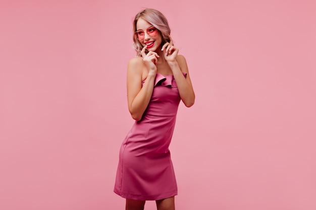 Mulher elegante e glamourosa em óculos de sol sorrindo na parede rosada