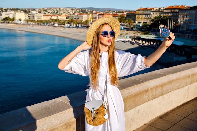 Mulher elegante e glamourosa usando vestido branco luxuoso e acessórios de palha fazendo selfie na praia