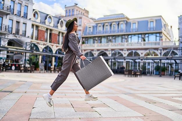 Mulher elegante e hippie viciada em compras com sacola de papel
