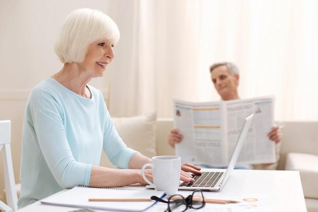 Mulher elegante e inspiradora que fica em casa enquanto conclui suas tarefas de trabalho usando seu laptop