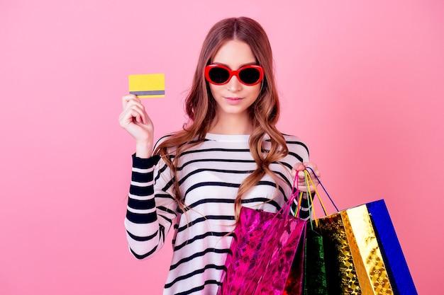 Mulher elegante e jovem atraente em um suéter listrado e óculos de sol vermelhos contém muitas sacolas de compras e cartão de crédito em um fundo rosa no estúdio. conceito de vício em compras e venda