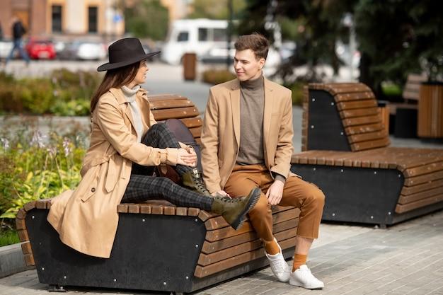 Mulher elegante e jovem feliz sentada no banco de madeira ao lado do namorado, enquanto os dois conversam durante o relaxamento no parque no fim de semana