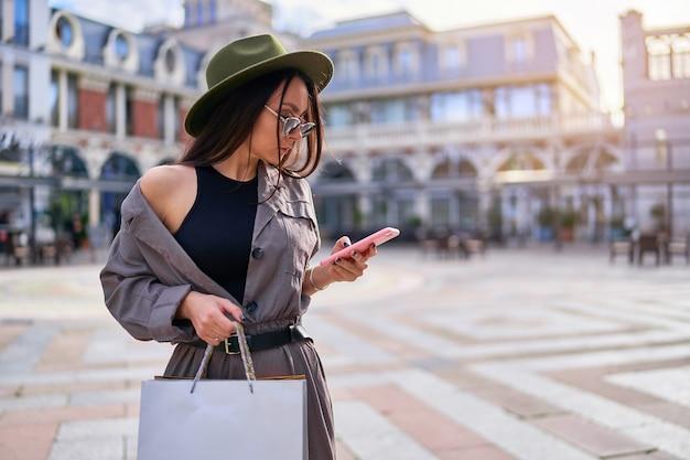 Mulher elegante e jovem hippie viciada em compras com sacolas de papel usando o telefone