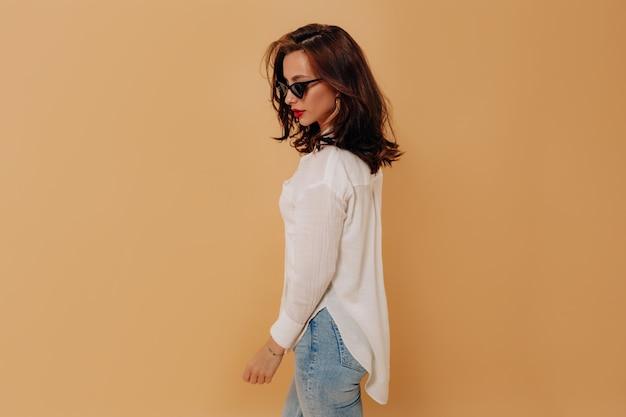Mulher elegante e moderna com cabelo escuro, camisa branca e óculos de sol pretos em pé sobre uma parede bege isolada