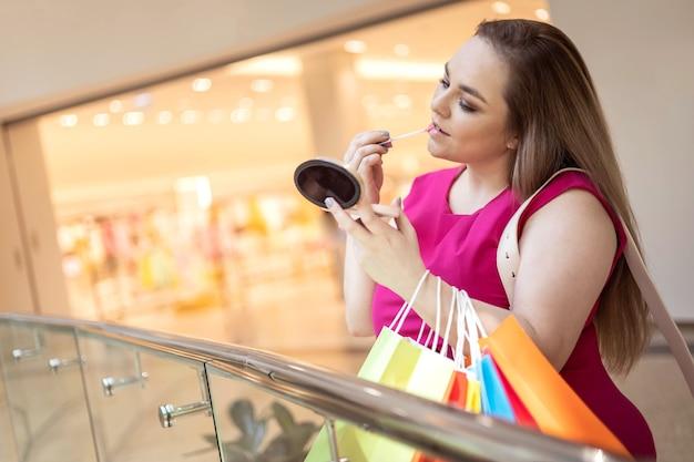 Mulher elegante e plus size aplicando brilho labial e aproveitando o desconto com uma sacola de compras no shopping center