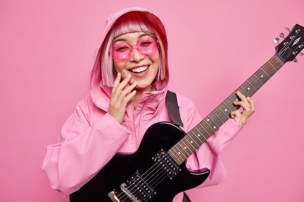 Mulher elegante e satisfeita vestida com uma jaqueta elegante, óculos de sol rosa se diverte fingindo ser estrela do rock sorri amplamente usa guitarra elétrica
