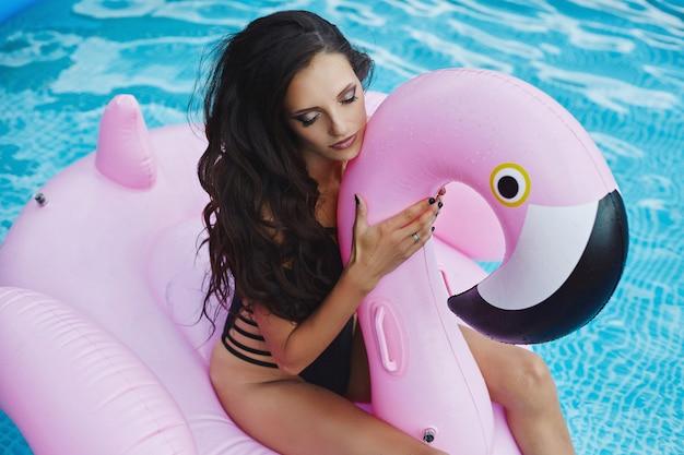Mulher elegante e sensual modelo morena com corpo sexy perfeito em biquíni preto elegante e óculos de sol glamourosos senta-se com os olhos fechados em um flamingo rosa inflável na piscina ao ar livre