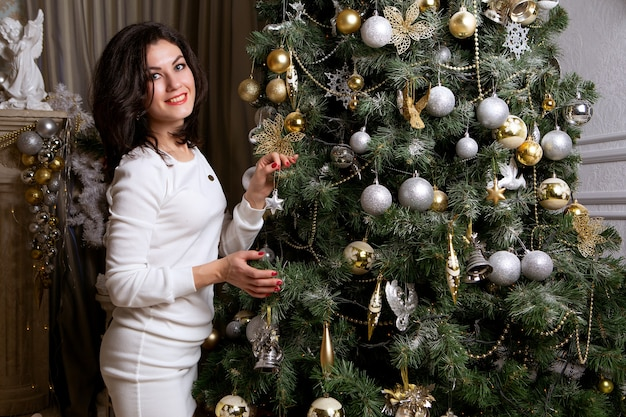 Mulher elegante e sorridente ao lado de uma árvore de natal
