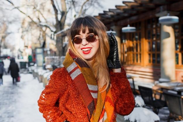 Mulher elegante e sorridente com óculos retrô posando ao ar livre
