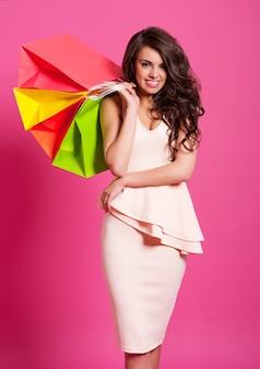 Mulher elegante e sorridente com sacolas de compras