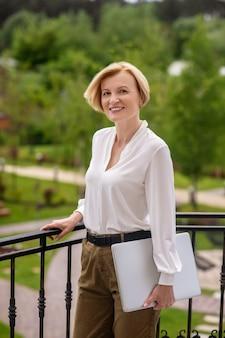 Mulher elegante e sorridente com um notebook em uma das mãos em pé ao lado da grade de ferro forjado