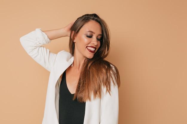 Mulher elegante e sorridente incrível com batom de vinho e jaqueta branca posando sobre uma parede bege, se preparando para a festa, parede isolada