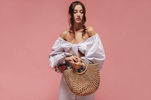 Mulher elegante e triste com cabelos ondulados em uma camisa leve de manga larga e saia legal olhando para baixo e segurando uma bolsa de palha com flores vermelhas