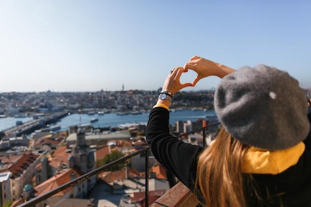 Mulher elegante em boina cinza com cabelos longos, de costas para a câmera contra a vista da cidade, com a forma de um coração com os dedos.