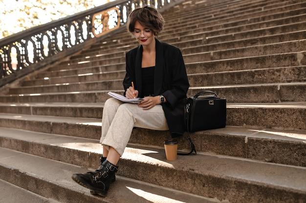 Mulher elegante em calças leves, jaqueta preta e botas se senta na escada do lado de fora. senhora de cabelos curtos de óculos, escrevendo ao ar livre.