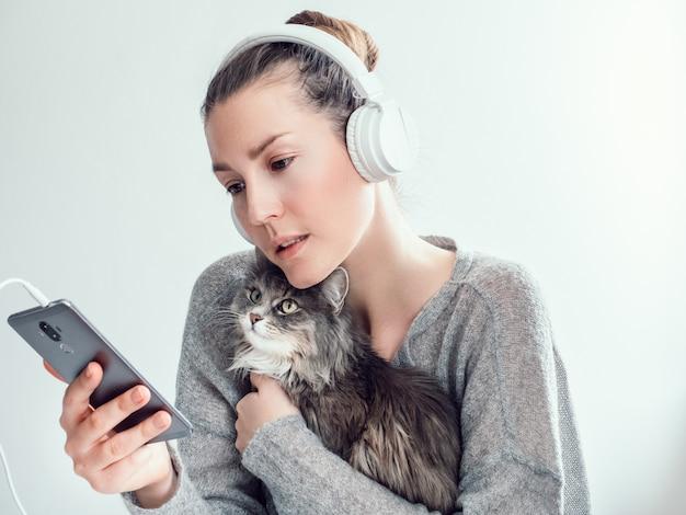 Mulher elegante em fones de ouvido e com seu gatinho