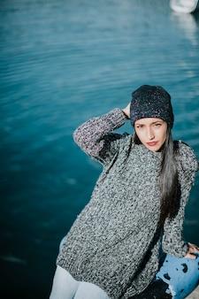 Mulher elegante em frente à água