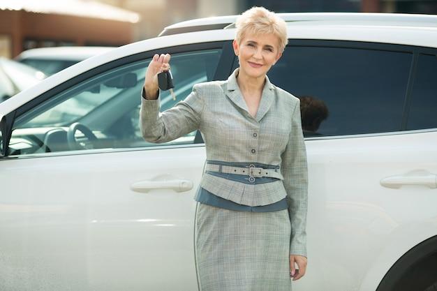 Mulher elegante em idade, de terno em pé perto de um carro no verão com as chaves nas mãos