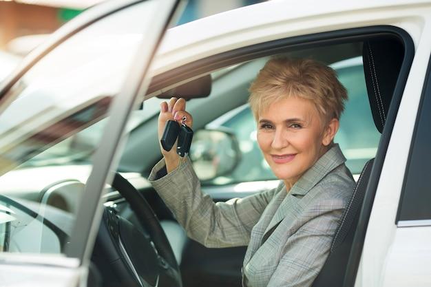 Mulher elegante em idade, de terno, sentada ao volante de um carro no verão com as chaves